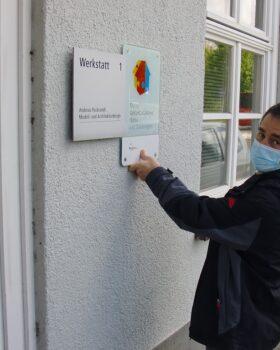 Mann hält Türschild mit dem Logo des Mehrgenerationenhauses hoch