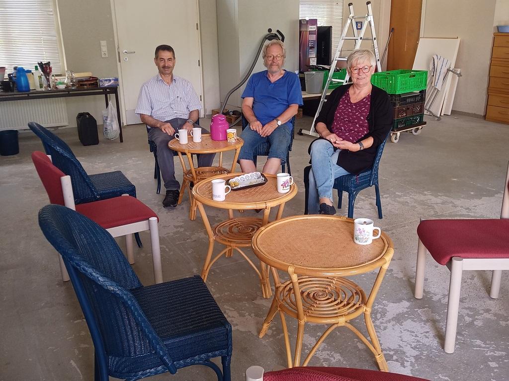 Blick auf den Cafébereich, in dem drei Menschen sitzen