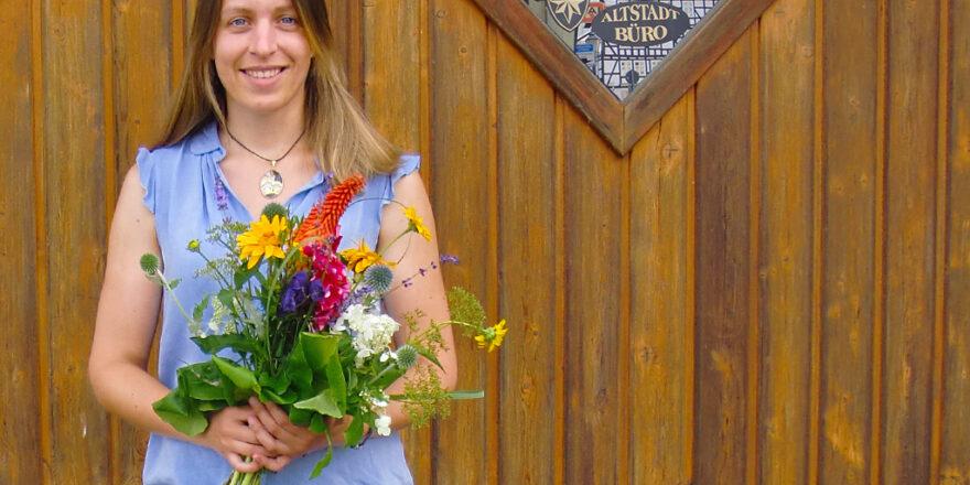 Frau steht mit Blumen in der Hand vor einer Holztür