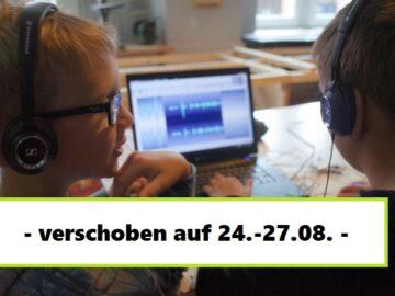 Zwei Jungen sitzen vor einem Laptop und schneiden eine Audiospur.